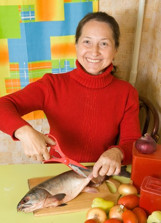 Mature woman cutting flippers with scissors in   kitchen photo