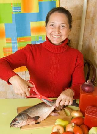 flippers: Mujer madura cortando aletas con tijeras de cocina  Foto de archivo
