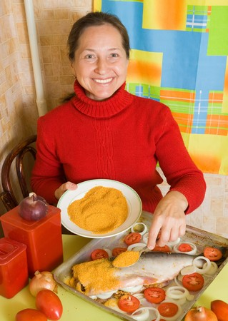 Mature woman is making breaded fish in cook griddle photo