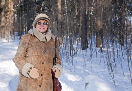 sheepskin: senior  woman in sheepskin coat goes for a walk on the wintry forest Stock Photo