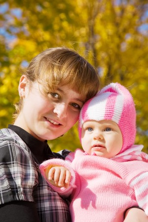 Portrait of mother with her baby in autumn park photo