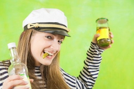 jack tar: Pretty female sailor with bottle of vodka and pickle over green background