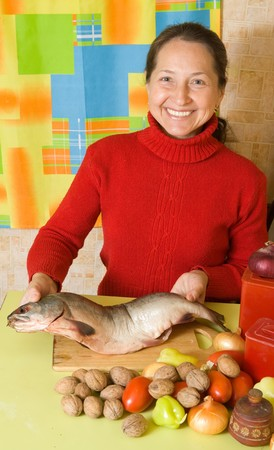 Mature woman is cooking red  fish  in kitchen photo