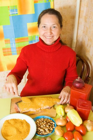 breading: Mature woman is breading red  fish  in kitchen