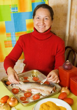 Woman cooking fresh  fish with onion and tomato  in  cook griddle photo