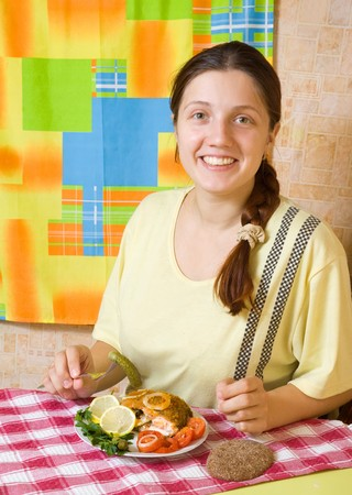 stuffed fish: Young woman eating stuffed fish in her kitchen