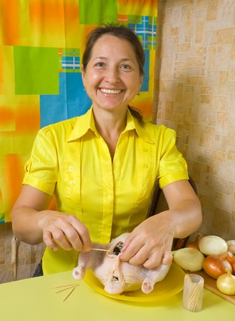 Mature woman sewing  chicken by toothpicks Stock Photo - 7997519