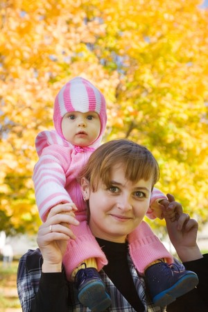 Happy mother with her baby against autumn nature Stock Photo - 8000628