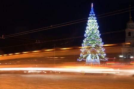traffic on night road against  illuminated  Christmas tree at night city Stock Photo