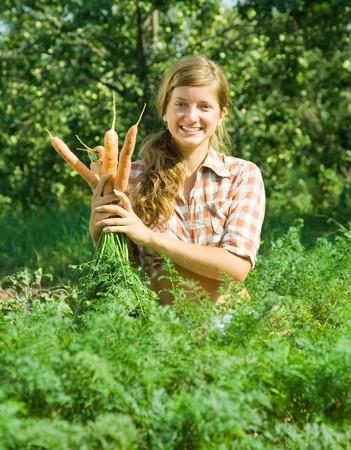 giovane donna è la raccolta di carota in campo Archivio Fotografico - 8000981