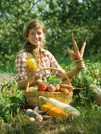 Teenage girl with basket of harvested vegetables photo