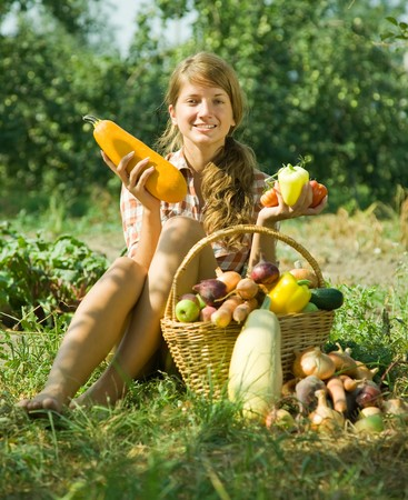 Young girl sitting with harvested vegetables ang fruits photo
