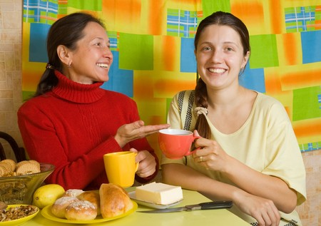 Mother and her adult dauther talking in kitchen Stock Photo - 8071640