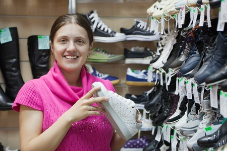 store interior: Girl chooses sporty shoes at shoes shop