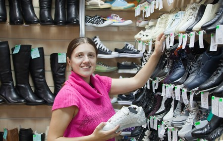 young woman chooses sporty shoes at shoes shop Stock Photo