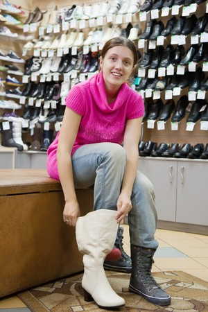 Girl chooses wintry shoes at shoes shop photo