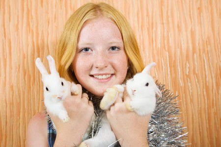 teenager girl in tinsel  with two pet rabbits