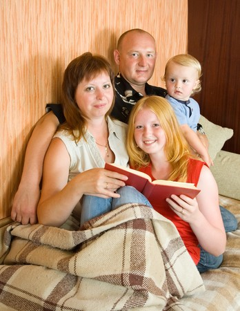 Father, mother and children reading  book at home photo