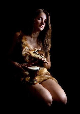neanderthal women: Female barbarian in foxcase with  tambourine at dark Stock Photo