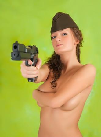 Topless girl in garrison cap with gun over green photo