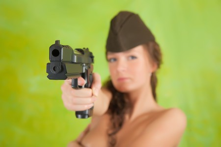 Topless girl  aiming a black gun over green. Focus on gun only photo