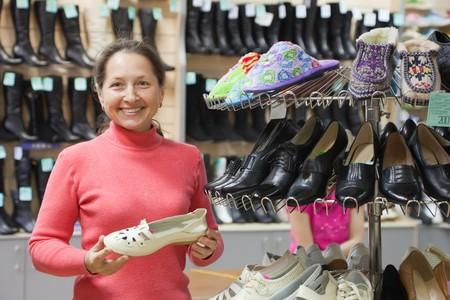 admixture: Mature woman chooses shoes at shoes shop