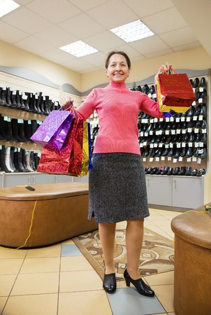 Happy mature woman with shopping bags at fashion shoe store Stock Photo - 8071786