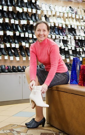 try: Mature woman trying shoes  for size  at shoes shop