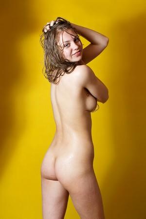 Desnudez chica húmeda sobre fondo amarillo en estudio