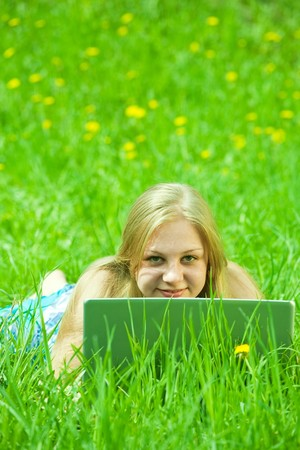 Young sweet girl relaxing with laptop outdoor photo