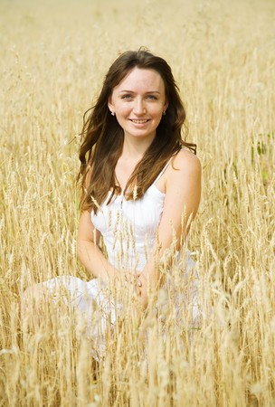 Happy girl in white dress at cereals field in summer photo
