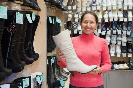 Mature woman chooses wintry shoes at shoes shop photo