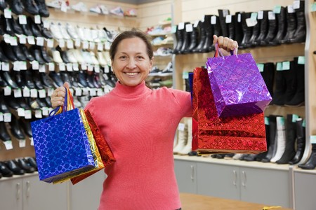 Happy mature woman with shopping bags at  shoes shop photo