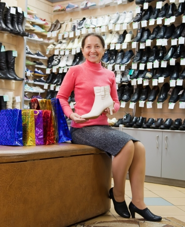 Mature woman shopping at fashion shoe store photo