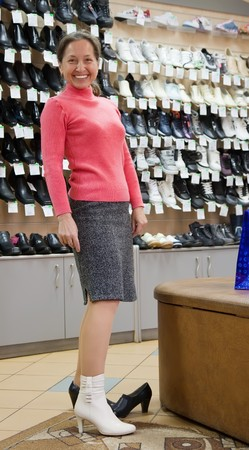 Mature woman trying shoes  for size  at shoes shop photo