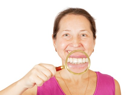 Teeth of mature woman through magnifier, isolated on white background. photo