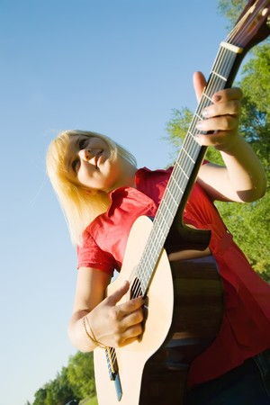 pretty girl playing guitar against blue sky photo