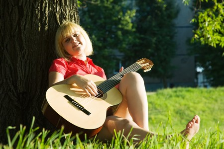 pretty girl playing guitar and relaxing in the park photo