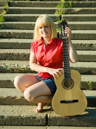 Blonde girl with guitar on steps of stair photo