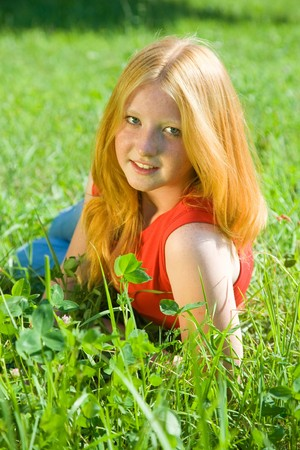 teener: Red-haired teen girl in red lying from meadow