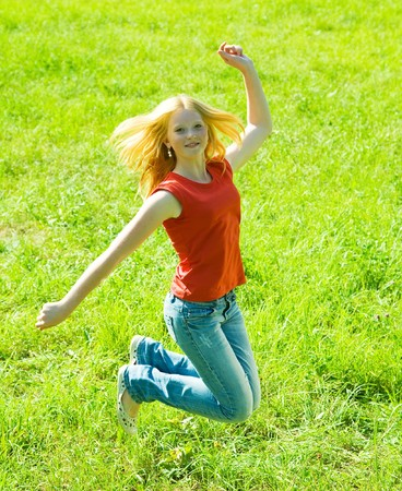 Jumping red-haired teen girl against green grass photo