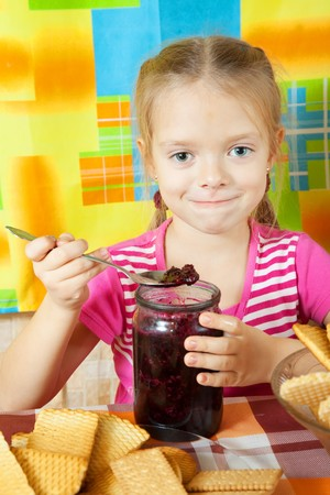 Little girl eating jam from  jar at kitchen Stock Photo - 8071978