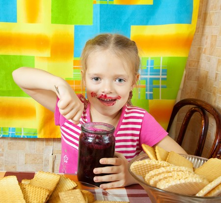 Little girl eating marmalade from  glass jar at kitchen Stock Photo - 8071977