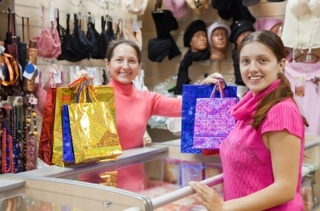 Buyer  and salesman  with purchases at  counter in underwear shop. Focus on buyer photo