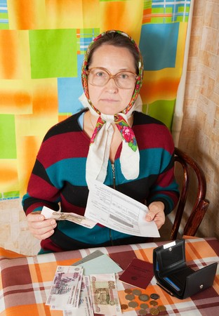 lamentable: sad elderly woman with bill and money  at home