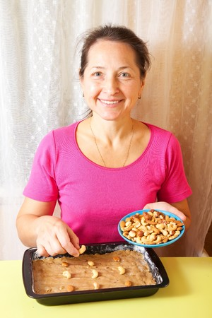 Mature woman adds nuts into dough.One of the stages of cooking of  honey cake.  See series Stock Photo - 8132572