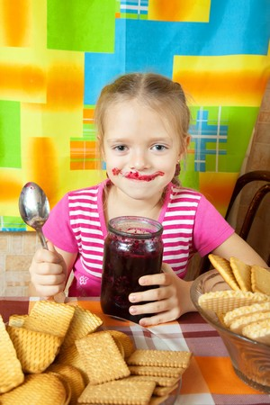 Little girl eating marmalade from  glass jar at kitchen Stock Photo - 8132601