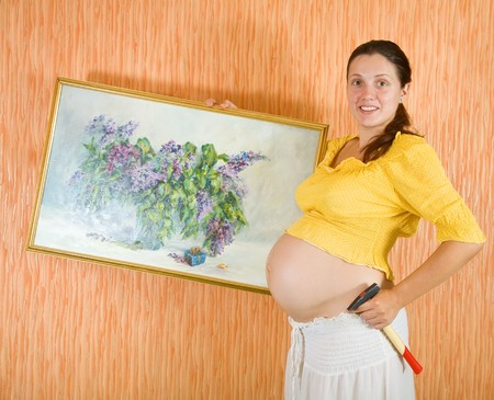 9 months pregnant woman decorating her room with art picture photo