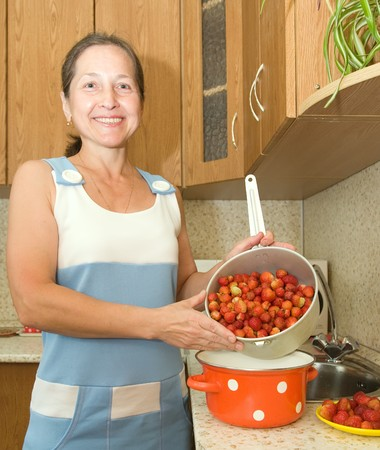 Woman making strawberry jam  in the kitchen photo