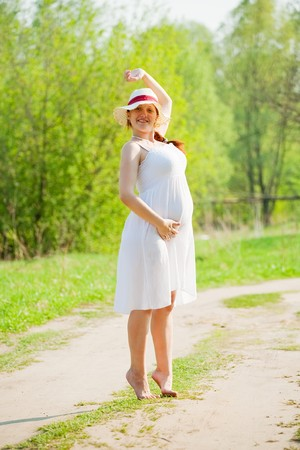 Portrait of 6 months pregnant woman on summer road Stock Photo - 8136209